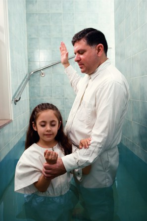 A young girl being baptized. She and the person performing the baptism wear white clothing to symbolize purity. Attendees at the baptismal service do not have to wear all white. They wear normal, modest clothing.